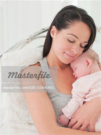 Bébé qui dort holding mère souriant
