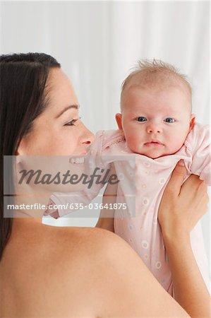 Sourire de bébé holding mère avec cheveux salissante