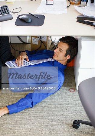 Businessman sleeping under desk in office