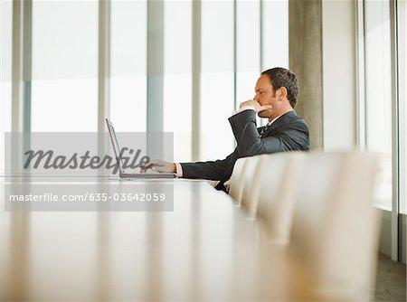Homme d'affaires travaillant sur ordinateur portable dans la salle de conférence vide