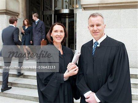 Souriant juges toge debout à l'extérieur du Palais de justice
