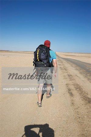 Vue arrière de l'homme, randonnée dans le désert du Namib, en Namibie