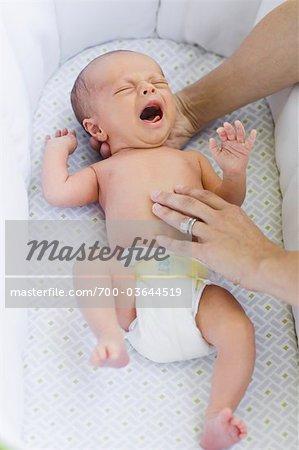 Mutters Hände mit Baby in der Krippe