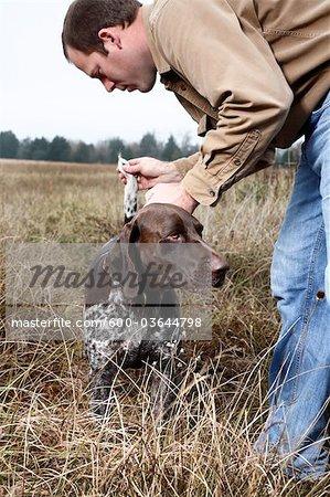 Man Checking Dog's Tail, Houston, Texas, USA