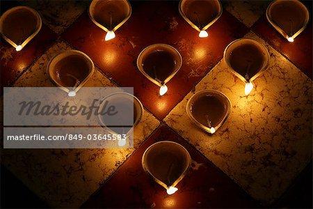 Lit oil lamps on tile
