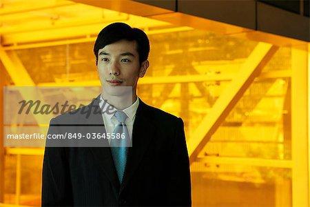 Jeune homme vêtu d'un costume devant orange vitres teintées