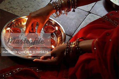 Gros plan d'une femme qui portait un sari, mettre des lampes à huile sur plaque argent