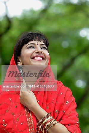 Femme indienne en levant et souriant avec sari rouge au-dessus de sa tête.