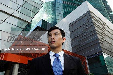 Jeune homme vêtu d'un costume devant des bâtiments modernes