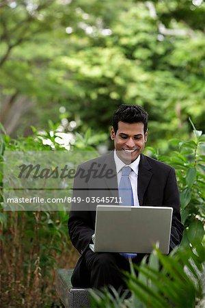 Homme indien travaillant sur ordinateur portable avec des plantes vertes et les arbres au premier plan et d'arrière-plan
