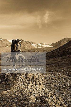 Male backpacker stops to view Gulkana Glacier while hiking in the Alaska Range, Southcentral Alaska, Summer/n
