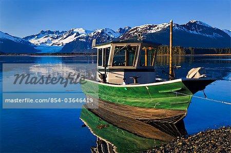 Vue panoramique d'un bateau de pêche amarré sur le canal de la rive de Gastineau Mendenhall Glacier et la chaîne côtière à l'arrière-plan, Inside Passage, sud-est de l'Alaska, Juneau, été
