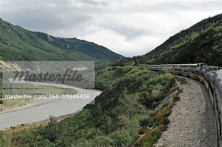 Malerischer Blick auf die Alaska Railroad Denali Star Zug entlang des Nenana River nördlich der Denali-Depot an einem späten bewölkten Nachmittag, Alaska Interior, Sommer