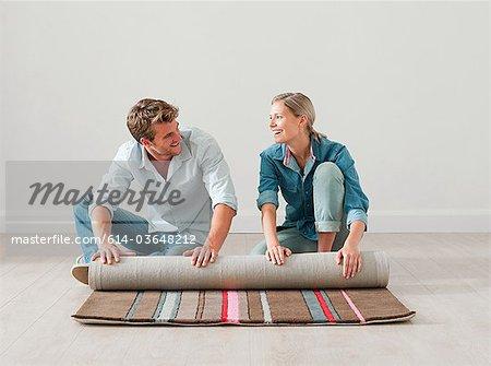 Young couple unrolling rug on floor
