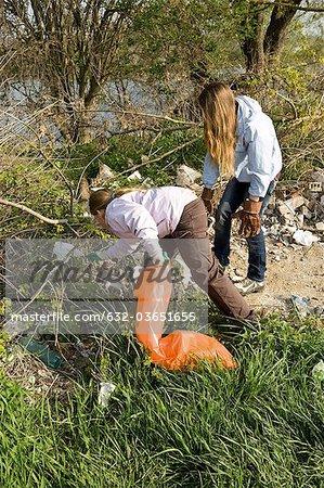 Girls picking up trash outdoors