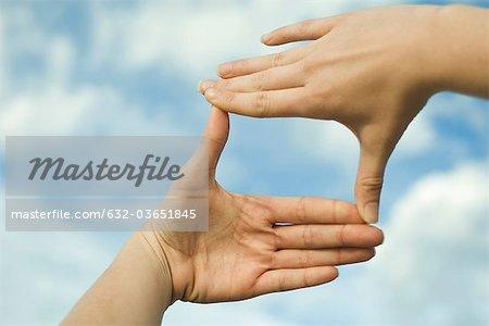 Mains faire un cadre de doigt devant le ciel