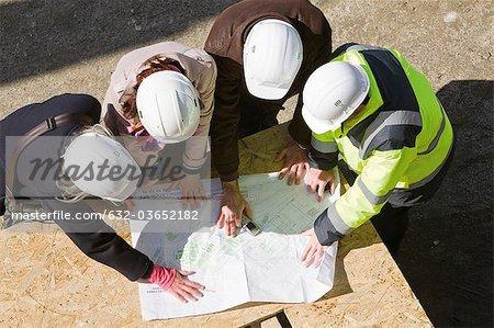 Architekten Treffen mit Bauunternehmer auf Baustelle Blaupausen zu überprüfen