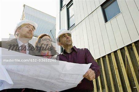 Bauunternehmer und Architekten diskutieren Blaupause auf Baustelle