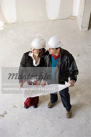 Architecte et entrepreneur en construction discutant blueprint