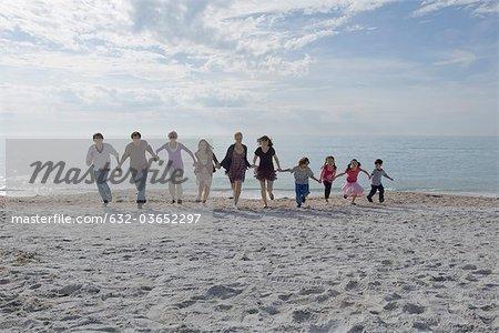Gruppe von Menschen Hand in Hand und zusammen laufen am Strand