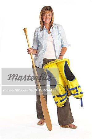 Portrait d'une femme portant un gilet de sauvetage et tenant une pagaie de canoë