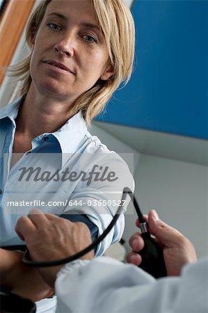 Médecin de la tension artérielle du patient en tenant
