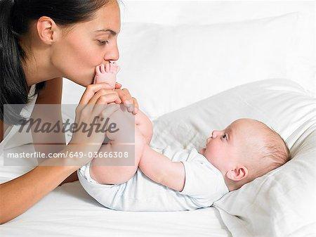 La mère s'embrasser les pieds de son bébé nouveau-né