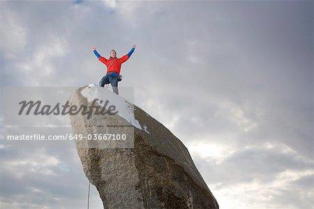 climber celebrating on snow capped peak