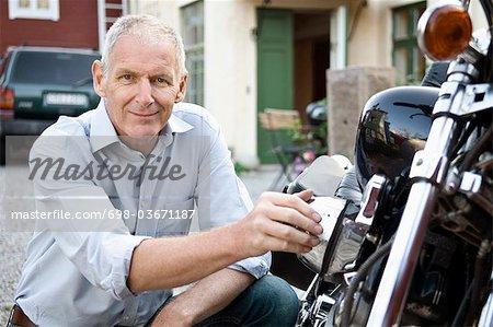 Man sitting next to his motorbike
