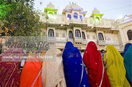 Women wearing colourful saris at the Mewar Festival on Lake Pichola, Udaipur, Rajasthan, India, Asia