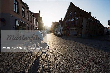 Coucher du soleil et l'ombre d'un cycliste sur pavées rue, vieille ville, patrimoine mondial de l'UNESCO, Bruges, Flandre, Belgique, Europe