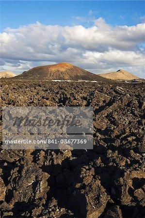 Unregelmäßige blockartige Lava (a'a) und Schlackenkegel der vulkanischen Landschaft der Nationalpark Timanfaya, Lanzarote, Kanarische Inseln, Spanien, Atlantik, Europa