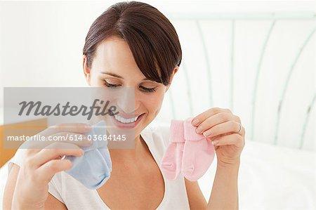 Femme enceinte, en regardant les chaussettes bébé bleu et rose