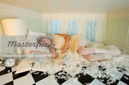 Jeune femme allongée parmi les plumes de l'oreiller en petite salle