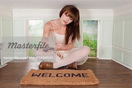 Jeune femme dans une petite pièce avec clé et tapis rouge