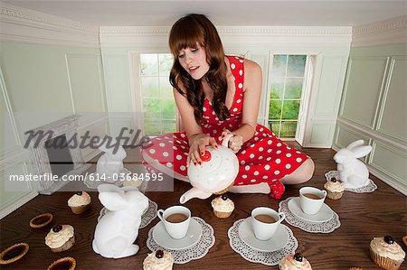 Junge Frau mit Tee-Party im kleinen Zimmer