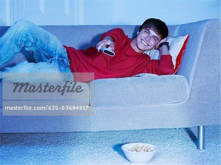 Adolescent souriant, couché sur le canapé avec télécommande