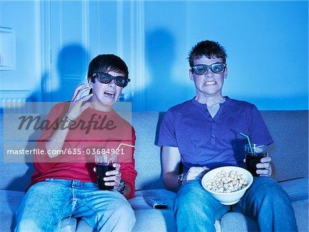 Adolescents avec des collations, regarder la télévision avec des lunettes 3D