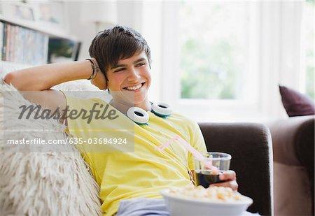Adolescent souriant assis avec pop-corn et soude