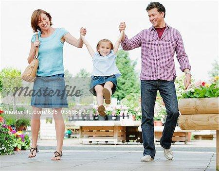 Parents swinging daughter in nursery
