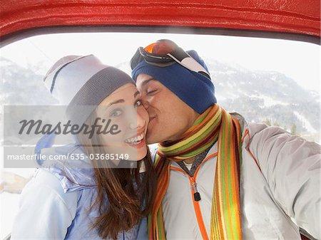 Man küssen Frau in Skilift