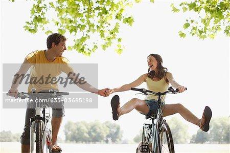 Couple heureux vélos d'équitation et main dans la main