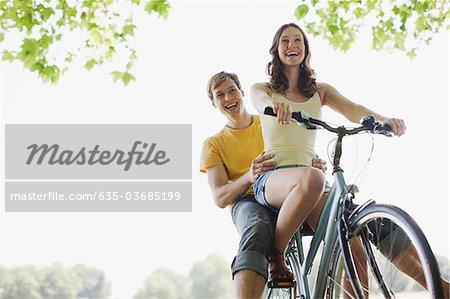 Lächelnd Frau Reiten Freund auf dem Fahrrad