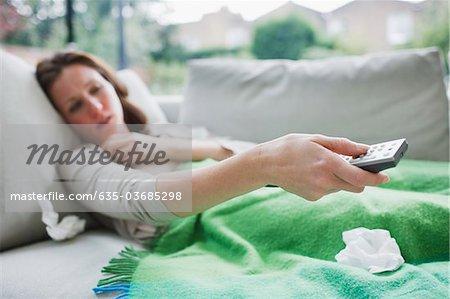 Femme malade couché sur le canapé, holding de contrôle à distance