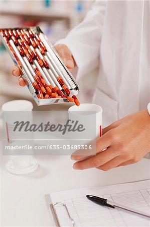 Apotheker in der Apotheke Pillen in Flasche messen