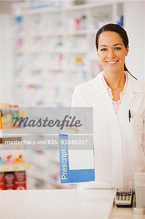 Pharmacist holding prescription in drug store