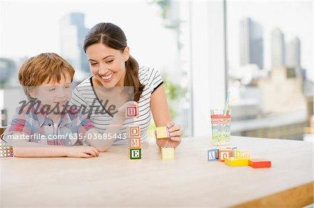 "Mutter Sohn Stapeln Alphabet Blöcke beobachten und Rechtschreibung """"zu Hause"""""