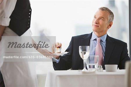 Businessman handing waitress credit card in restaurant