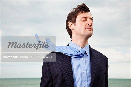 Vent souffle cravate homme d'affaires près de l'océan