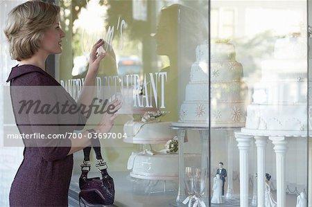 Femme regardant les gâteaux de mariage à travers la vitrine
